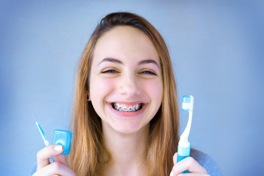 Young girl with long straight light brown hair smiling with braces while holding a tooth brush and floss.