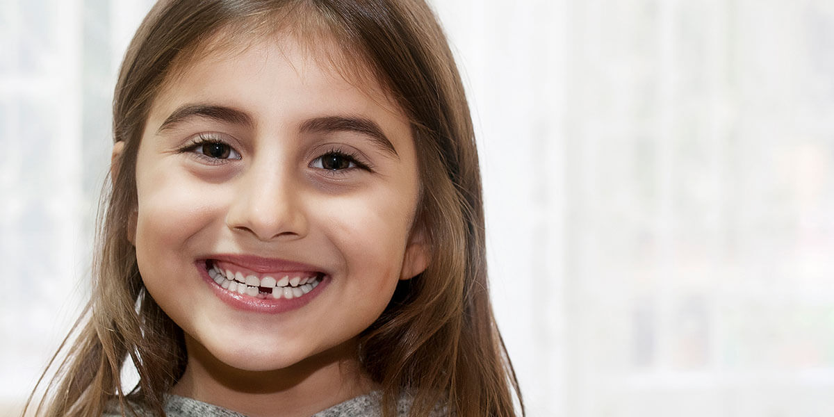 Smiling girl with lower front tooth missing