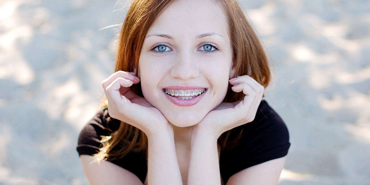 Young lady with braces smiling and holding her face in both hands