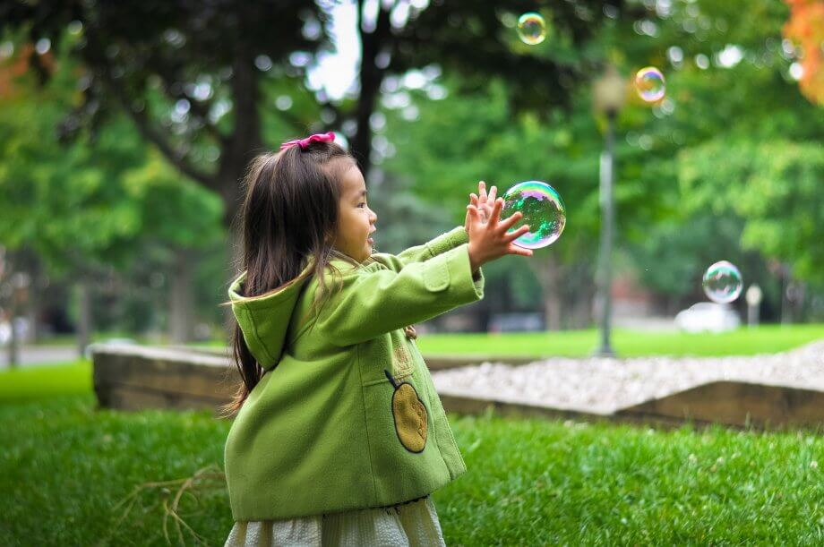 Young girl playing in a park getting ready to burst a bubble.