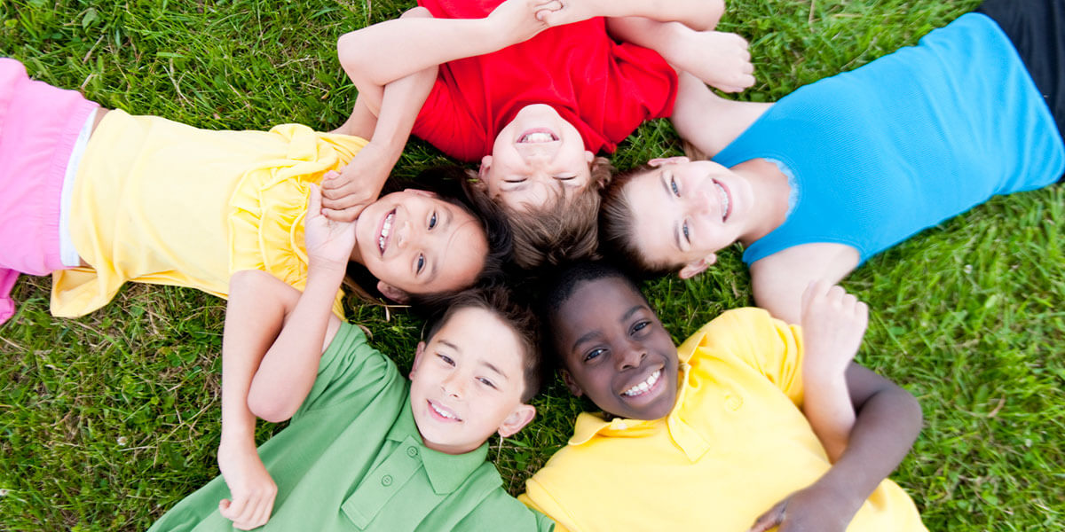 Kids in group locking arms while laying on the ground