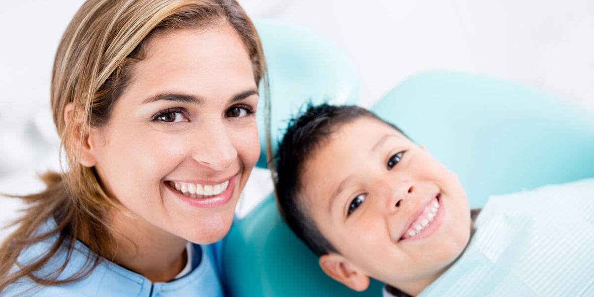 Smiling dental assistant and young boy smiling in dental chair