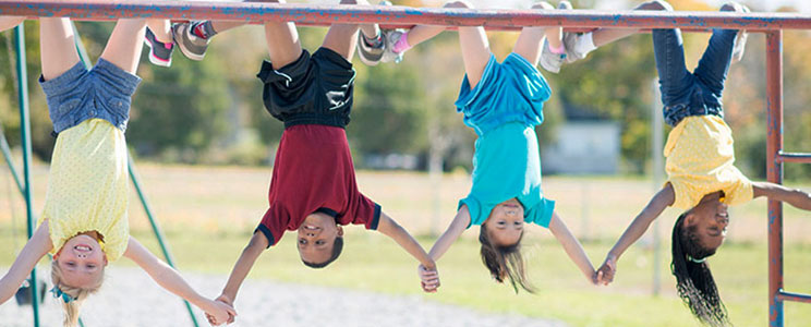 Kids holding hands while hanging upside down from the monkey bars