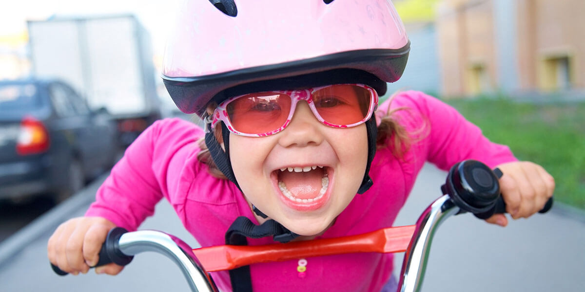 Young girl with pink helmet riding bike